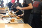 MOOYAH Burgers Fries Shakes Team Members preparing burger orders